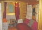 a roulotte de Shanti, couchage lit banquette à droite et alcôve avec lit 160 au fond